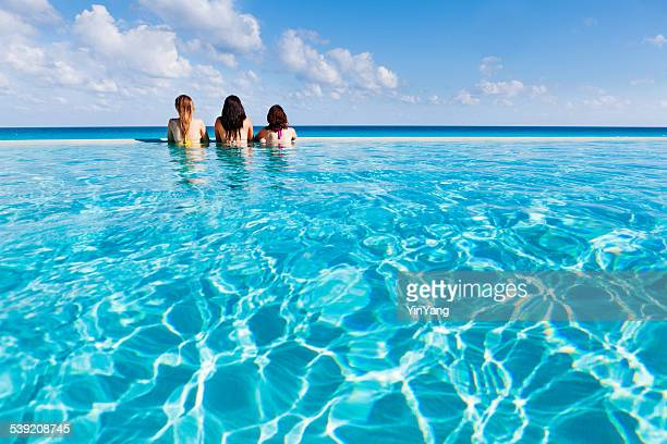 Mujeres jóvenes disfrutar de Piscina sin límites de paraíso Tropical