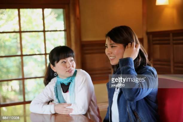 Young women enjoying talk in cafe
