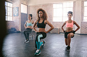 Portrait of young women exercising in aerobics class. Three females doing workout together in gym.