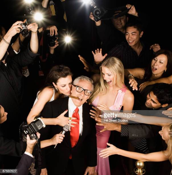 Young women fawning over old male celebrity