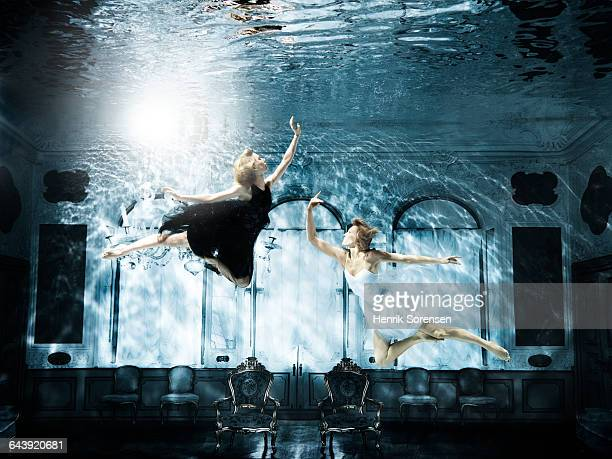 2 young women floating gracefully under water