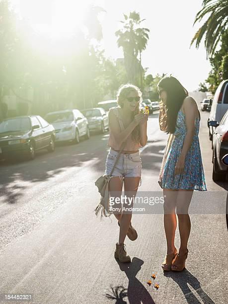 Young women friends walking along street