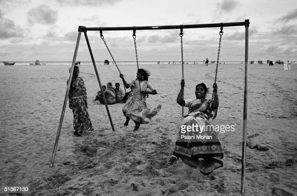 Young women from rural Indian on a day trip to the city play on a swing on Marina Beach in December 2002 in Madras India Marina's long stretch of...