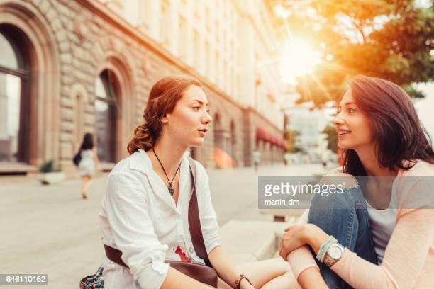 Young women gossiping outside