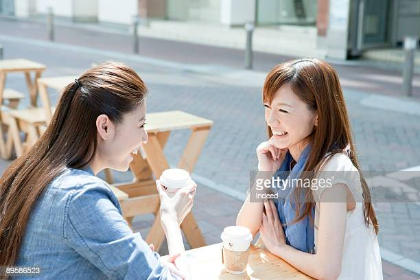 Young women having coffee, smiling face to face