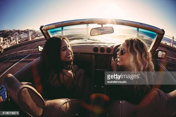 Young women having fun in convertible on seaside at sunset