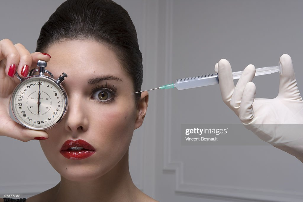 young women holding a stop watch with a syringe