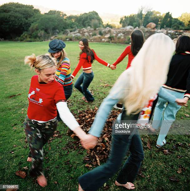 Young women holding hands playing ring-around-a-rosy