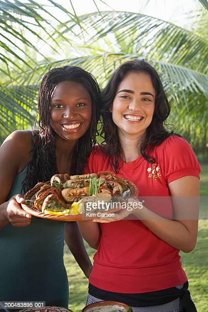 Young women holding platter of cooked crab, portrait