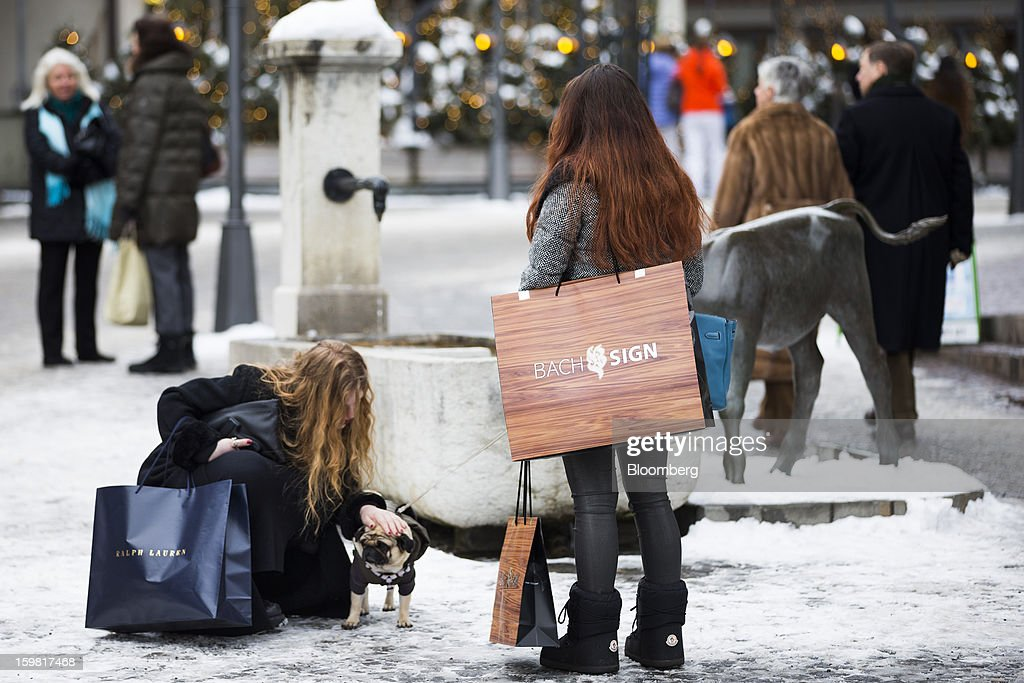 Young women holding shopping bags pause to pet a dog on the promenade in Gstaad, Switzerland, on Saturday, Jan. 19, 2013. Options traders are pushing the cost of bearish wagers on Swiss shares to the lowest level in almost seven years amid optimism a decline in the franc versus the euro will benefit the nation's exporters. Photographer: Valentin Flauraud/Bloomberg via Getty Images