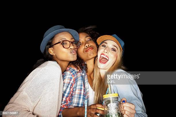 Young women huddled together holding mason jars looking at camera puckering lips
