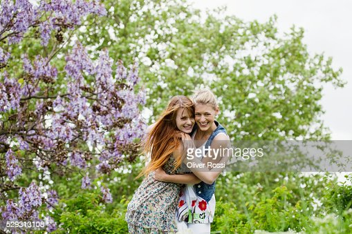 Young women hugging outdoors : Stockfoto