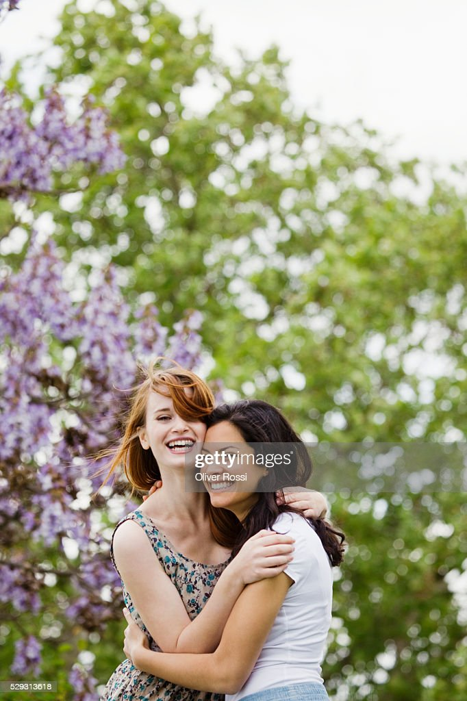 Young women hugging outdoors : Bildbanksbilder