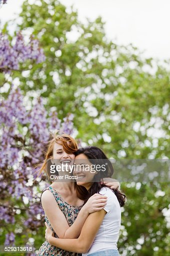 Young women hugging outdoors : Stock Photo