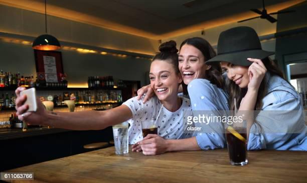 Young women in bar taking selfie