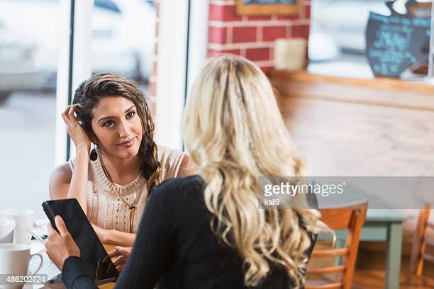 Young women in coffee shop with digital tablets talking