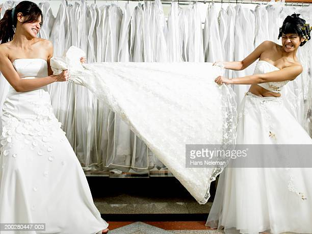Young women in fitting room tugging at gown