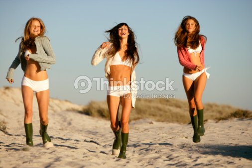 a8c5e0abc4 Young women in galoshes and swimsuits running on beach together : Stock  Photo