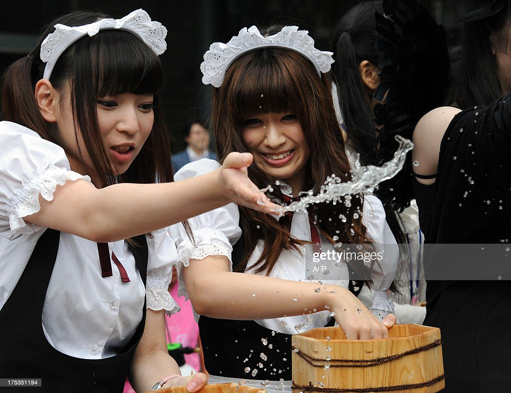 Young women in maid costumes throw water to the ground in Akihabara shopping district in Tokyo on August 3, 2013. Over 500 people including 50 maid-costumed young women who work at 'maid cafes' took part in the annual summer event to cool off the street.