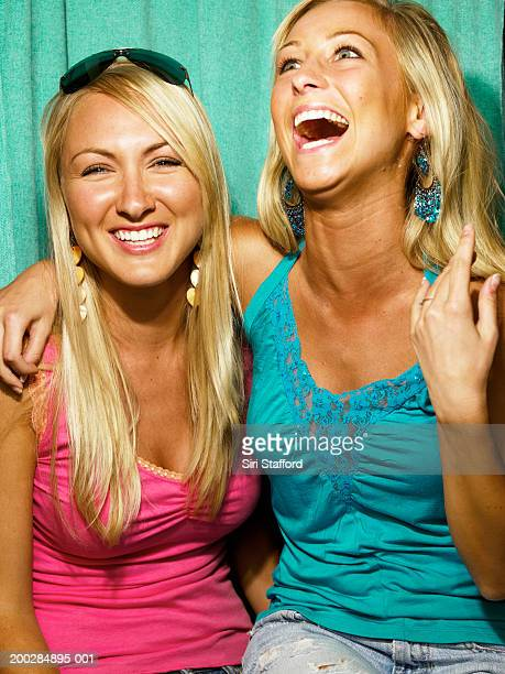 Young women in photo booth, laughing
