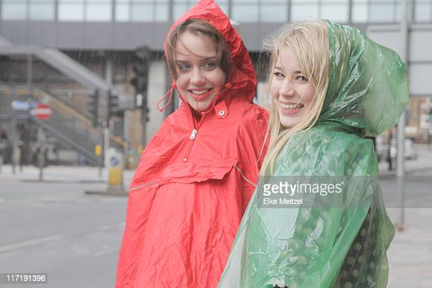 2 young women in raincoats in the city