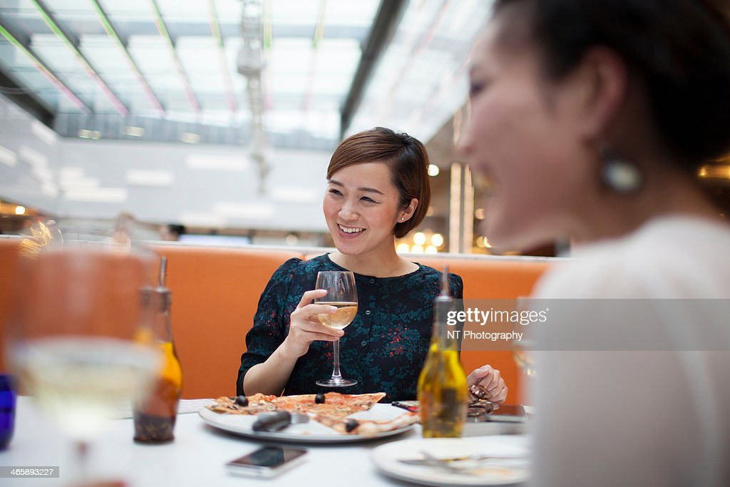 Young women in restaurant eating pizza : Stock Photo