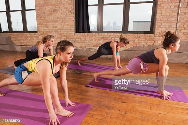Young Women in Runner's Pose Attending  Group Yoga Class
