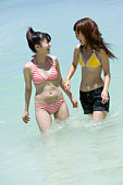 Young women in swimwear walking in the sea, smiling, Saipan