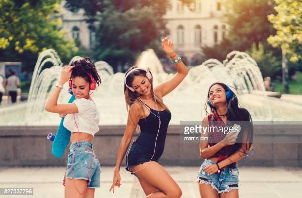 Jeunes femmes dans la ville, dansant sur la musique