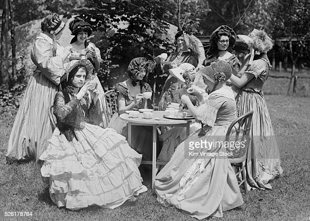 Young women in the early 20th century dress up in clothes from the mid 19th century and have a tea party in the yard
