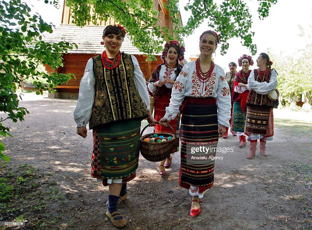 Young women in Ukrainian traditional clothes carry the basket with Easter eggs during folk Easter Tradition of pouring water called 'Pouring Monday' in open air Cossack village 'Mamaeva Sloboda', Ukraine,on May 02, 2016. The tradition of pouring water when single guys pour unmarried girls by water is celebrated on the first Monday after Orthodox Easter.