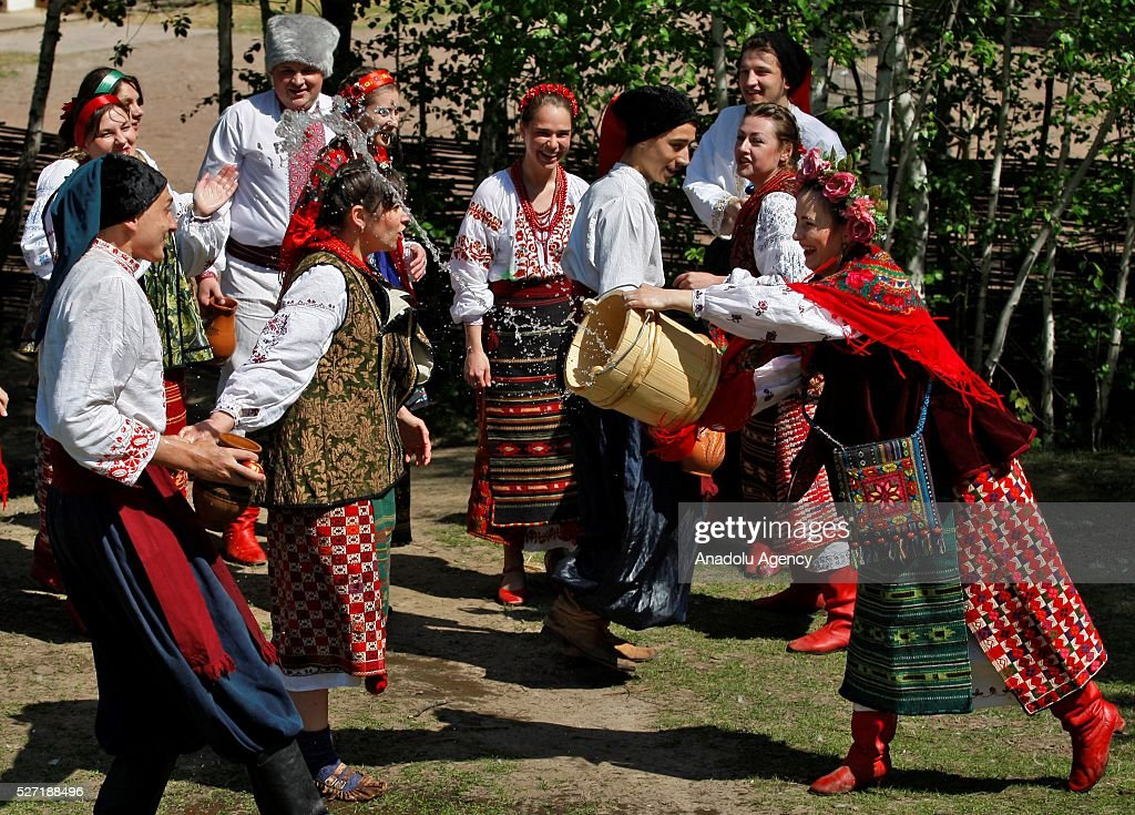 Young women in Ukrainian traditional clothes pour water on the men during folk Easter Tradition of pouring water called 'Pouring Monday' in open air Cossack village 'Mamaeva Sloboda', Ukraine,on May 02, 2016. The tradition of pouring water when single guys pour unmarried girls by water is celebrated on the first Monday after Orthodox Easter.