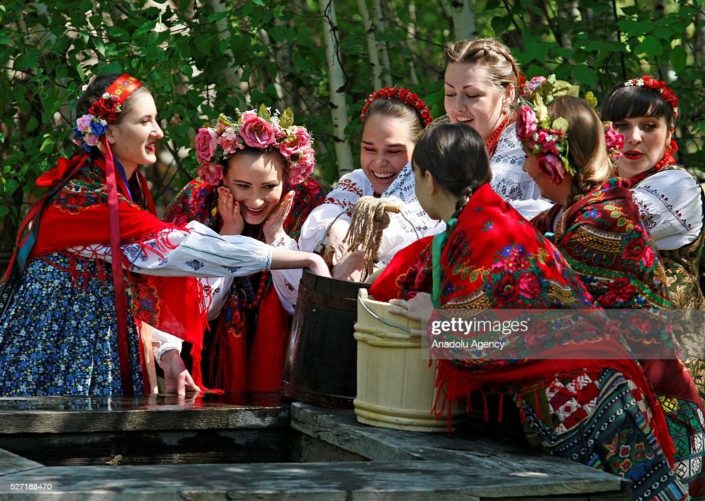 Young women in Ukrainian traditional clothes wash up near a well during folk Easter Tradition of pouring water called 'Pouring Monday' in open air Cossack village 'Mamaeva Sloboda', Ukraine,on May 02, 2016. The tradition of pouring water when single guys pour unmarried girls by water is celebrated on the first Monday after Orthodox Easter.