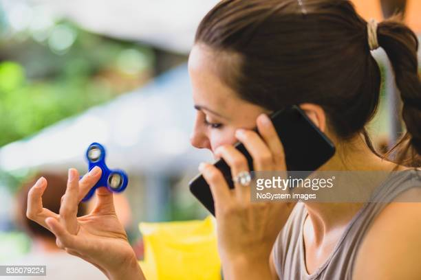 Young women is playing with fidget spinner in cafe.