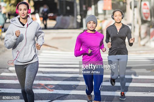 Young women jogging on city street
