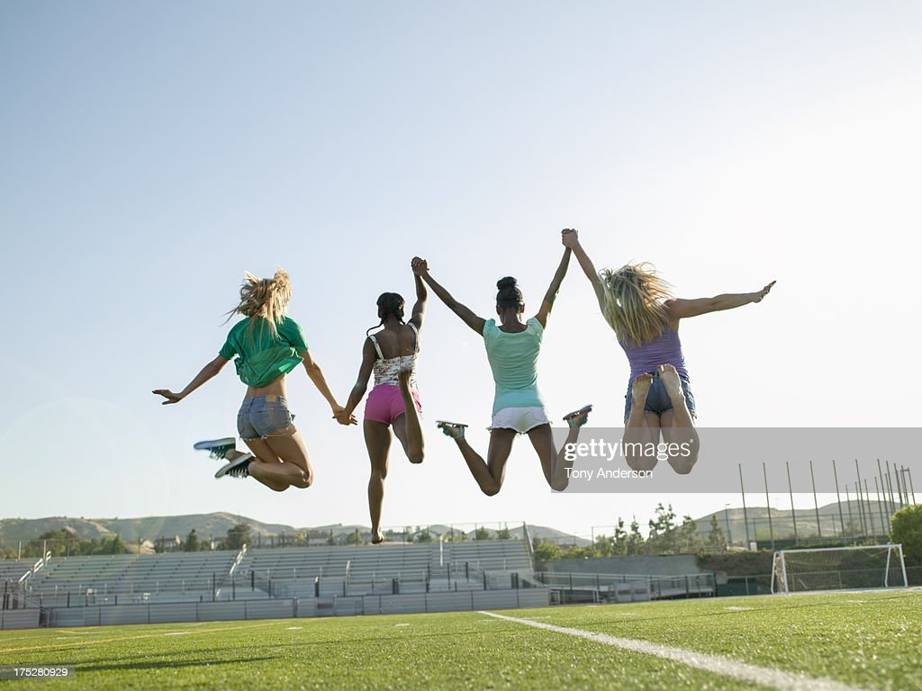 Young women jumping for joy on field : Stock Photo