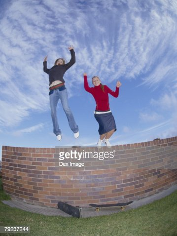 Young women jumping from wall, arms outstretched : Stock Photo