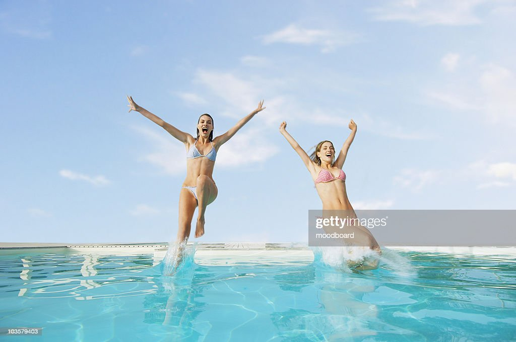 Young Women Jumping into Swimming Pool, front view : Stock Photo