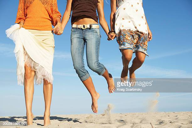 Young women jumping on beach, low section