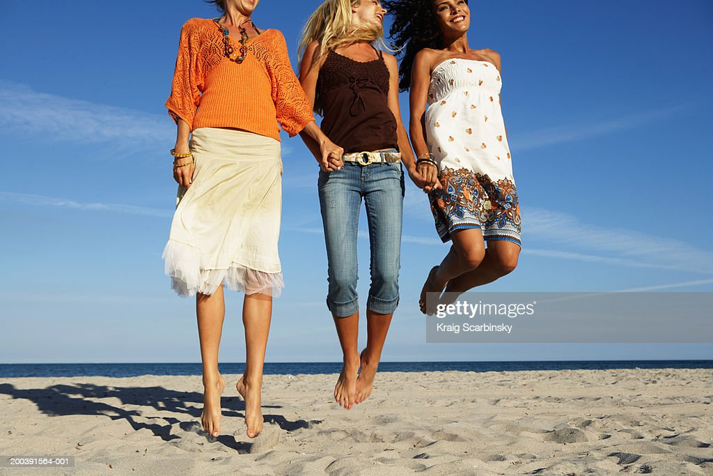 Young women jumping on beach, smiling, low section