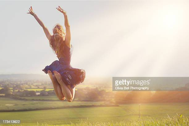 Young women jumping towards sunshine