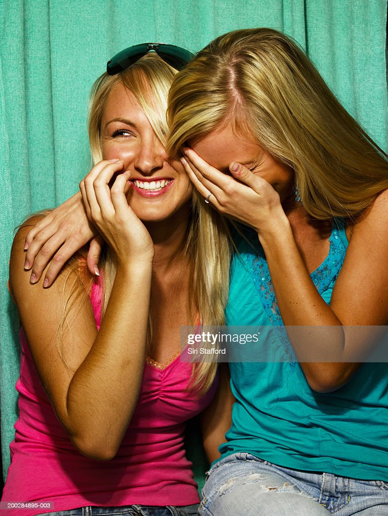 Young women laughing in photo booth : Stock Photo