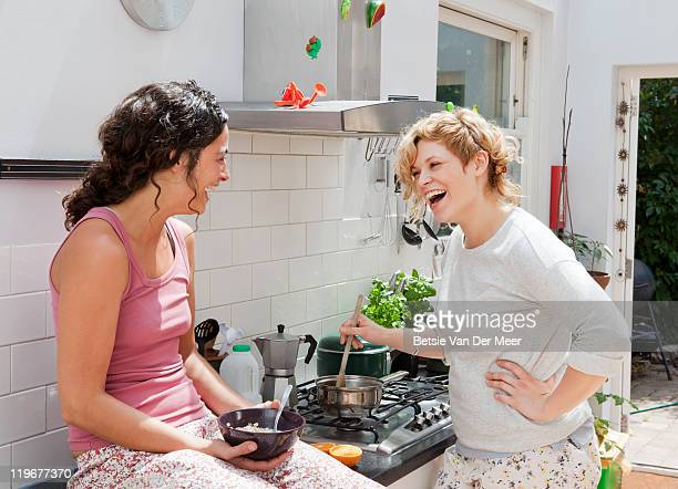 Young women laughing, while preparing breakfast.