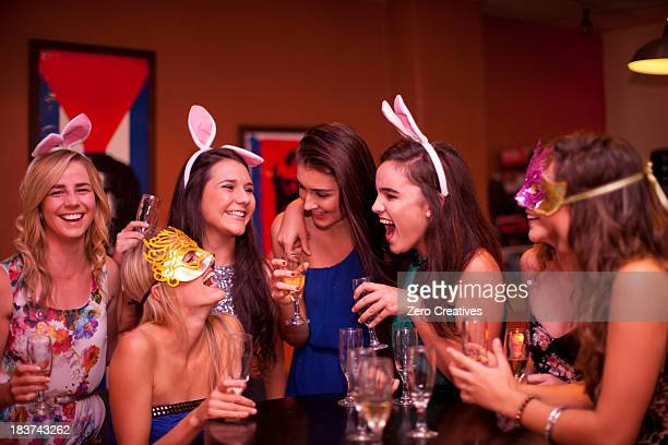 Young women laughing with drinks at hen party