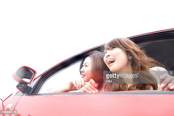 Young women leaning out of a car