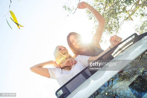 Young women leaning out of a sunroof