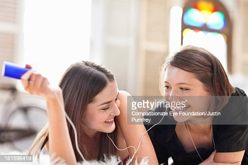 Young women listening to music on mp3 player : Stock Photo