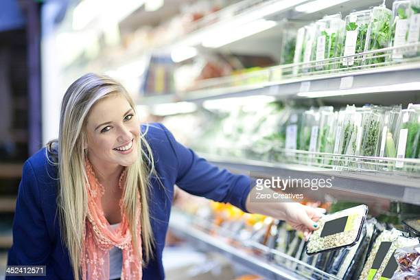 Young women looking at herbs in supermarket