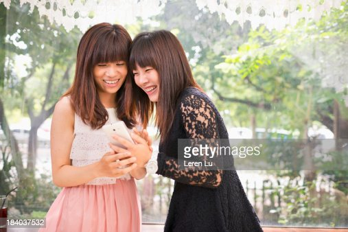 Young women looking at smartphone happily : Stock Photo