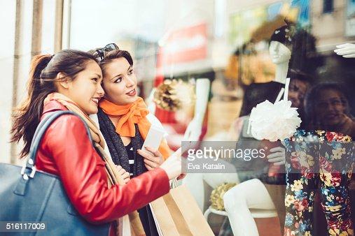 Mujeres jóvenes buscando los productos mostrados en escaparates